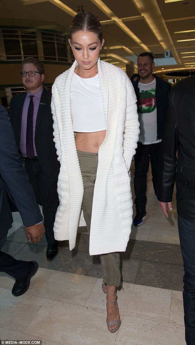 Cute and casual:The 20-year-old looked cute, casual and cosy in a white crop top teamed with olive green three-quarter length trousers, an oversized knitted cardigan and some stone-coloured strappy stilettos