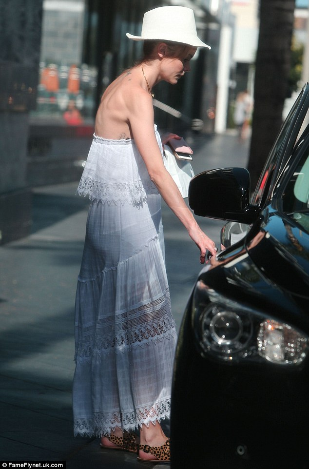 Summer chic: The star was clad in a lightweight white maxi dress which she wore with a matching hat