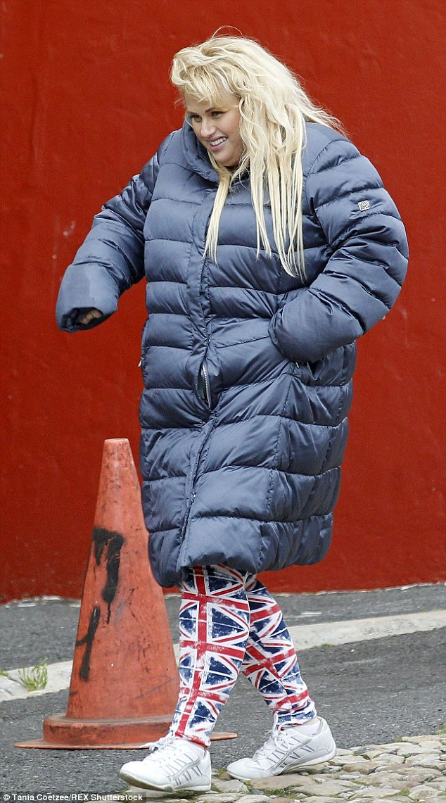 Nice and snug: Rebel Wilson donned a grey padded jacket and Union Jack print leggings as she filmed scenes for new Sasha Baron Cohen comedy Grimsby in Cape Town, South Africa