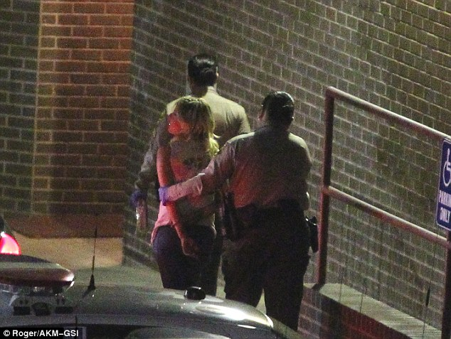 Off to jail: Dudley is seen being led away in handcuffs after being detained outside the hotspot