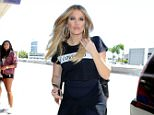 """Khloe Kardashian looks salon fresh and wears a t-shirt with the print """"I love you"""" paired with hoop earrings and capri leggings as she catches a flight out of LAX with little sister Kendall Jenner. Wednesday, August 5, 2015. X17online.com"""