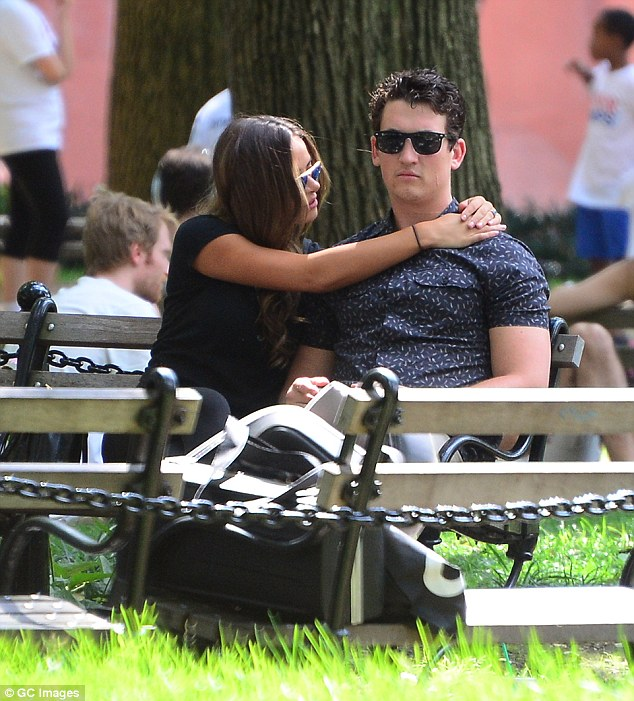 Hands on: The stunning brunette placed her arms around Miles' shoulders as the pair listened to band music