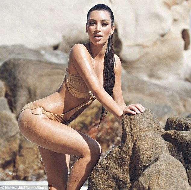 Curves on show: Kim Kardashian tweeted some more sexy snaps today, posing in a monokini while seductively posing against a rock
