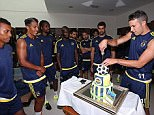 Robin van Persie cuts the birthday cake given to him by Fenerbahce while his new team-mates watch on
