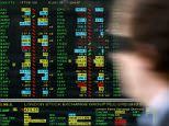 A worker walks past a screen displaying stock market movements at a window of the London Stock Exchange in the City of London October 27, 2008. The top share index slid by more than 4.5 percent early on Monday, as increasing anxiety about the state of the global economy hit embattled banks and demand worries sent energy and mining stocks tumbling.  REUTERS/Alessia Pierdomenico (BRITAIN)