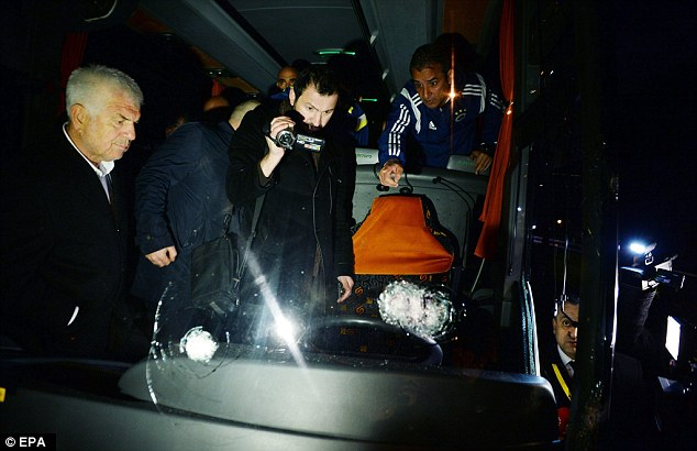 Fenerbahce coach Ismail Kartal (right) points to the bullet holes as a policeman inspects the damage