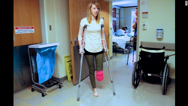 Adrianne Haslet-Davis walks using crutches outside her hospital room a week after the attacks.