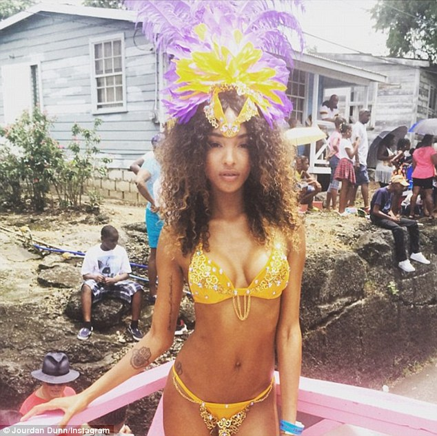 Party time: Jourdan recently spent time in Barbados at the Kadooment Day carnival, wearing a striking little yellow bikini and feathered headdress