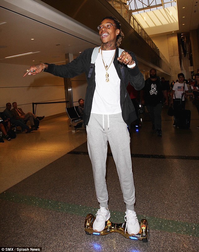 Ready to ride:The rapper is pictured here enjoying a ride on his golden scooter at the same airport on Tuesday