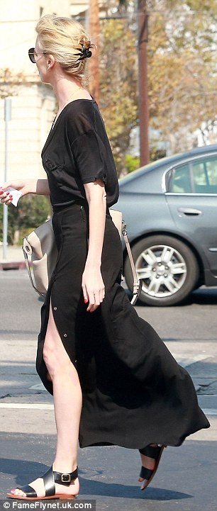 Fashionista: The Mad Max: Fury Road star strut her stuff in black sandals and concealed her eyes behind glamorous cat-eye sunglasses