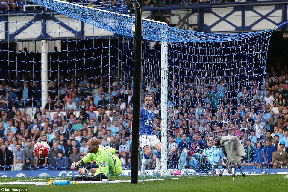 Kolarov falls to the ground as his shot finds the back of the net and Howard (left) and Cleverley (centre) can only watch on