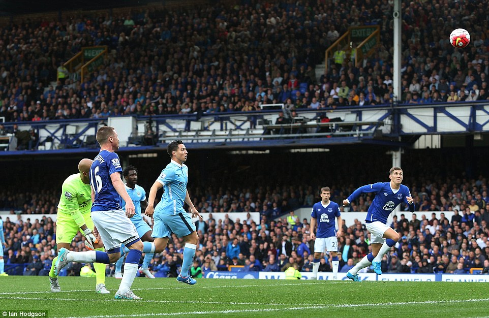The ball floats as if in slow motion as Nasri's momentum takes him beyond Howard who, along with Stones (right) watches it into the net