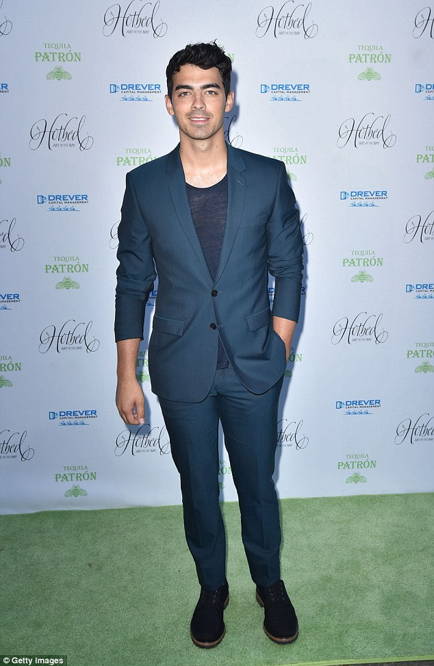 Ultra handsome: Joe looked sharp in his deep blue suit and semi-sheer top as he arrived for co-hosting duties