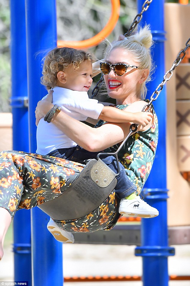 Mommy's got you! The blonde beauty held tightly to son Apollo as she played on the swings