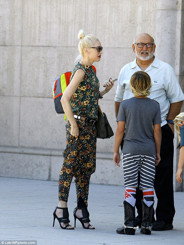Deep in conversation: The star hung around after church to chat with her father, who sported a loose-fitting, short-sleeved button down, black trousers, and coordinating dress shoes