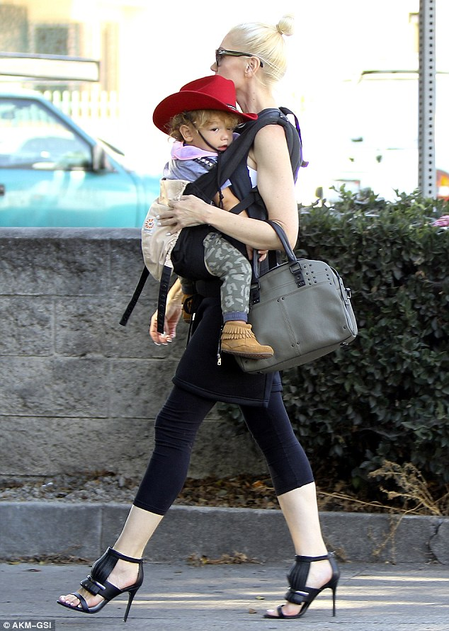Doting: At times The Voice judge was spotted holding youngest son Apollo in a carrier strapped across her chest
