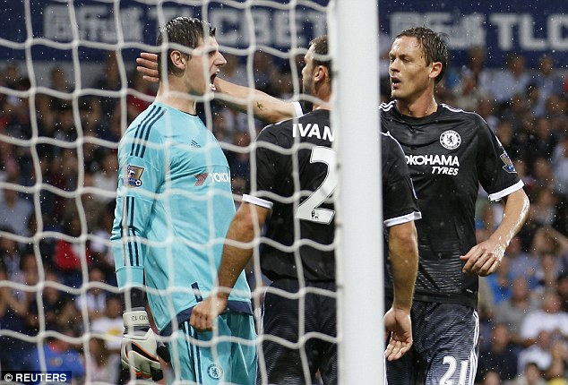 Courtois is congratulated for his stop during Sunday's clash between Chelsea and West Brom in the rain
