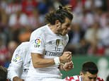 Real Madrid's Gareth Bale, center, jumps and heads the ball by Sporting's Sergio Alvarez, center right, during a Spanish La Liga soccer match between Real Madrid and Sporting de Gijon at the 'El Molinon' stadium in Gijon, Spain, Sunday, Aug. 23, 2015. (AP Photo/Jose Vicente)