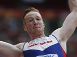 """Britain's Greg Rutherford competes in the qualifying round of the men's long jump athletics event at the 2015 IAAF World Championships at the """"Bird's Nest"""" National Stadium in Beijing on August 24, 2015.  AFP PHOTO / ADRIAN DENNISADRIAN DENNIS/AFP/Getty Images"""