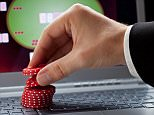A stock photo of poker chips on a laptop.  Player placing chips on a laptop which shows an online casino - online gambling concept; focus on the chips.  CF9TJE