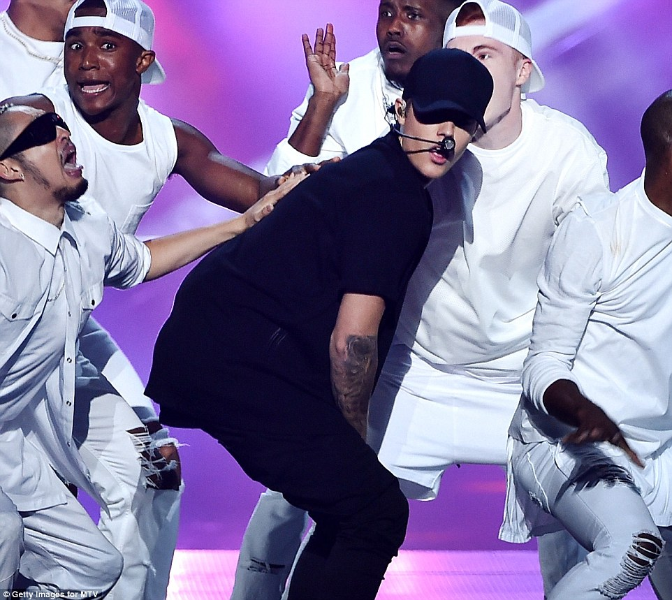 Loving it:  Justin Bieber looked like he was enjoying performing with these strapping young gentlemen despite delivering off-key vocals