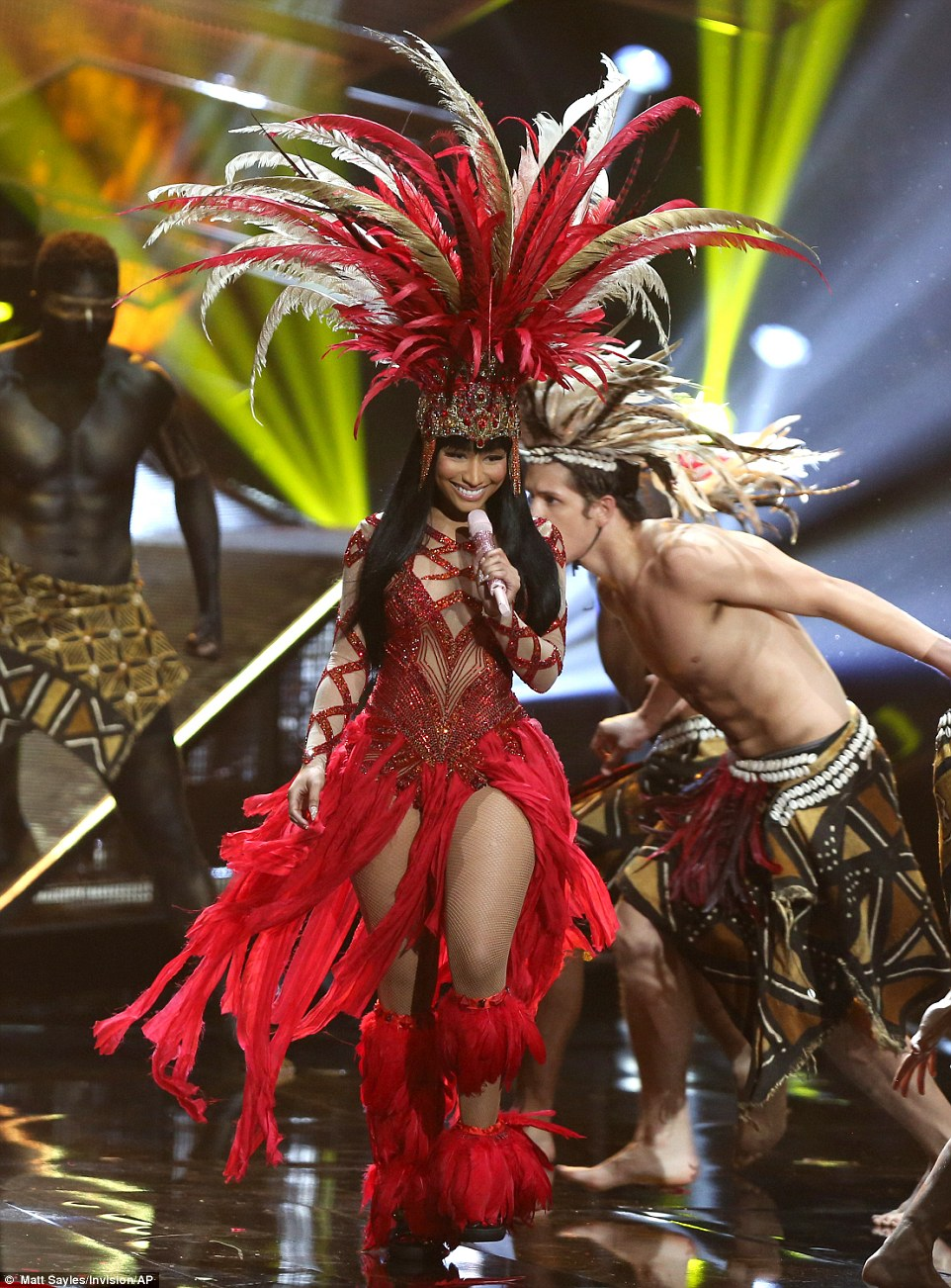 Tribal dancing: She wore an ostentatious headdress while her backing singer's wore faux ethnic dress