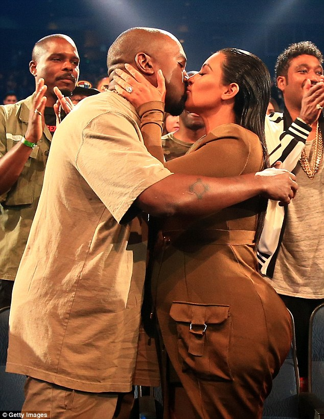 Special moment: Kanye and wife Kim shared a kiss before he accepted his award on Sunday night
