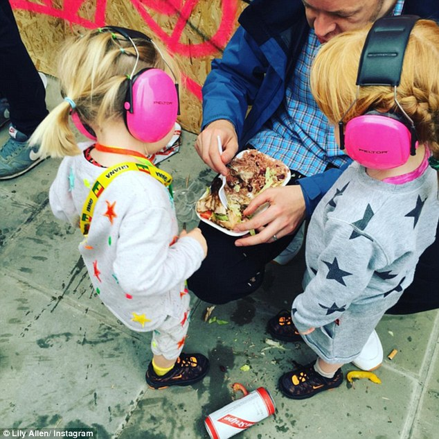 Fun for all the family: On Sunday, Lily was having a more relaxed time at the Carnival, sampling some street food with her daughters Ethel and Marnie