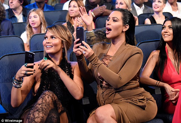 Proud wives: Chrissy Teigen and Kim Kused their phones to snap photos as their husbands picked up their award