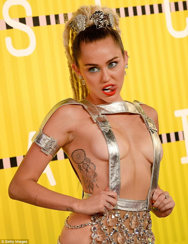 There's that famous tongue: It just had some strategically placed shiny suspenders over her breasts and embellished cloth over her bare bum