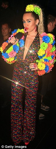 Putting on a show: Miley left all her inhibitions behind when she hosted the 2015 MTV VMAs in a panoply of eccentric costumes, including chandelier embellished suspenders (L), a more conservative spangled jumpsuit (C) and a cut-out pom-pom dress (R)