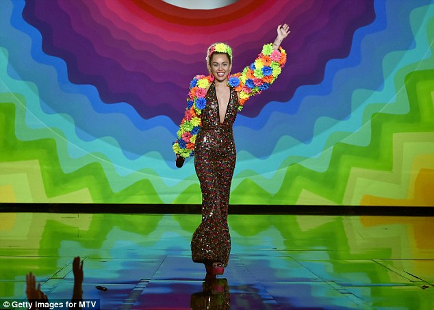 Flower power: Miley wore a multi-coloured coat as she greeted the audience
