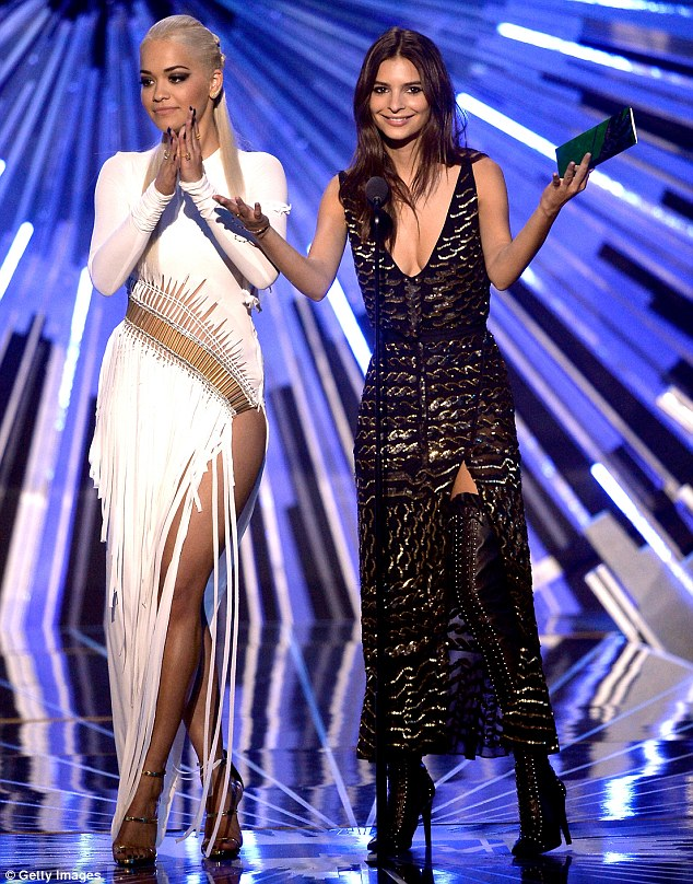 You wouldn't want to get make-up on that! Ora changed into a skin-tight white frock to co-present an award with Emily Ratajkowski...but full sleeves meant that her tattoos were still covered up