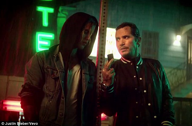 Shenanigans: The video opens with the singer meeting a tattooed John Leguizamo in a torrential downpour, as the two make a shady looking transaction