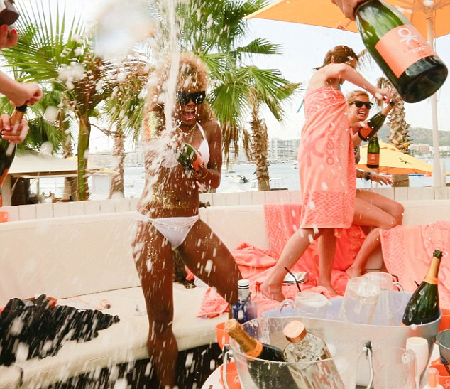 Champagne showers: Within seconds, Fleur is covering fellow partygoers in the fizzy beverage