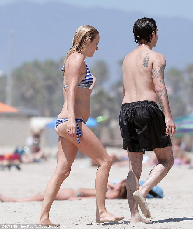 Going with the flow: The 40-year-old trailed behind her boyfriend and towards the beach towels