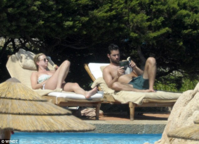 Sunbathing: The couple kicked back in lounge chairs by the pool as well, this time as Josh was spotted reading a book