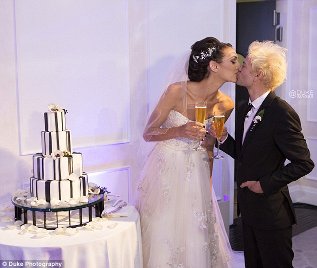 New start: The newlyweds shared a kiss by their black-and-white wedding cake