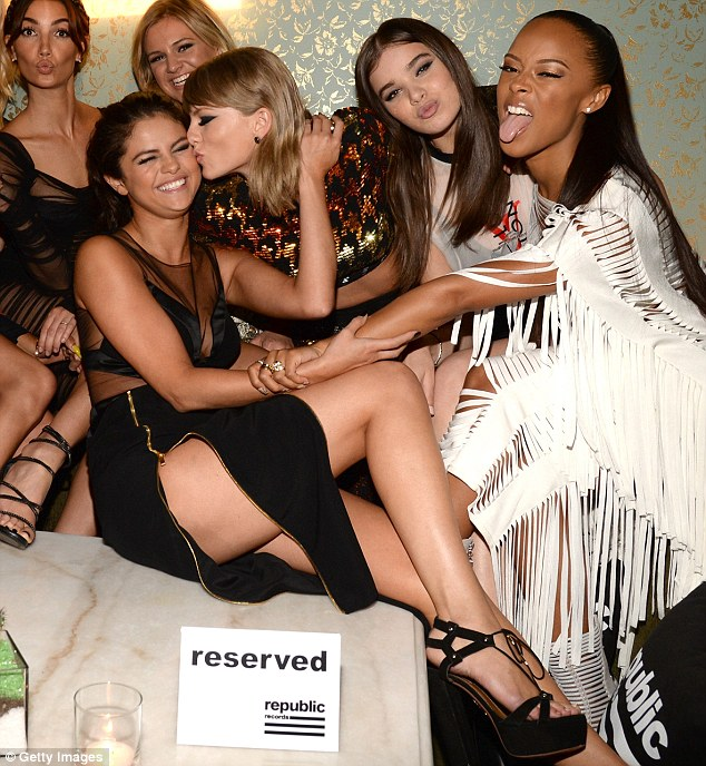 She's not reserved: Taylor Swift could not resist smooching her sidekick as her 'squad' watched on with glee