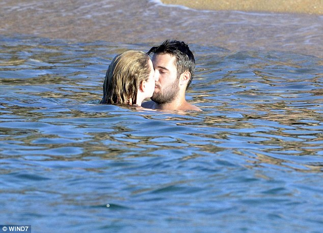 Tactile display: The doting couple couldn't quite keep their hands off each other as they were spotted cuddling, play fighting in the water, and pausing to share a romantic kiss