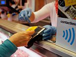 A woman pays on a butchery with a contactless credit card system in the island of Majorca, Spain.