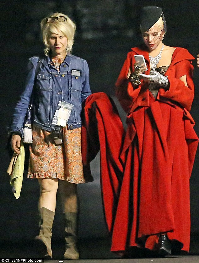In character: The blonde star, who seemed entranced by her phone, certainly looked the part in the floor-length number, which is perfect attire for the chilling TV show