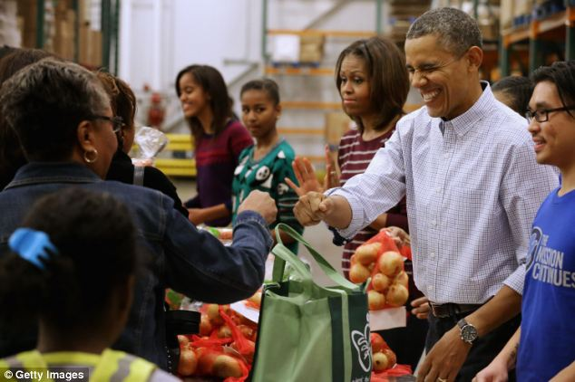 Helping hand: On Wednesday, Obama, Michelle and their daughters Sasha and Malia helped distribute bags of food to needy children and seniors at the Capital Area Food Bank in Washington D.C.