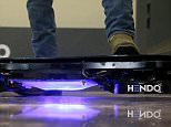Arx Pax engineer Garrett Foshay stands over a Hendo Hoverboard in Los Gatos, California.  Skateboarding is going airborne this fall with the launch of the first real commercially marketed hoverboard which uses magnetics to float about an inch off the ground.      In this Oct. 30, 2014 photo,  (AP Photo/Jeff Chiu)
