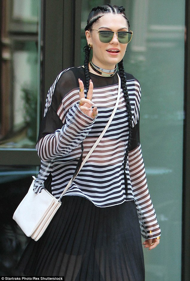 Stylish as ever: The 27-year-old rocked a chic semi-sheer blouse and a coordinating pleated skirt