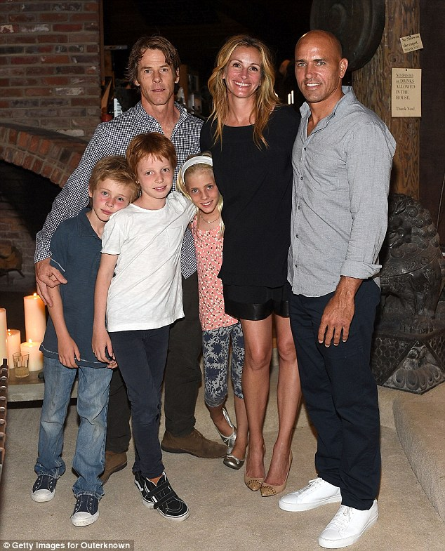 Family portrait: Last weekend, Roberts joined her husband Danny Moder and their three soccer-loving children - twins Phineas & Hazel, 10, and son Henry, 8 - at surfer Kelly Slater's (R) Outerknown clothing launch in Malibu