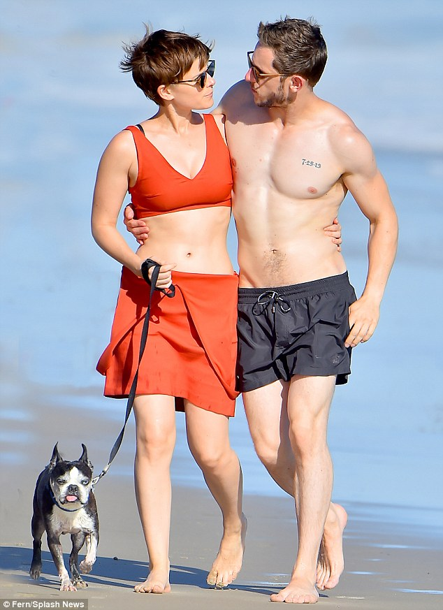Close:Their arms wrapped around one another, the two snuggled up as close as they could, gazing into one another's eyes and talking closely as they strolled on the sand in Malibu