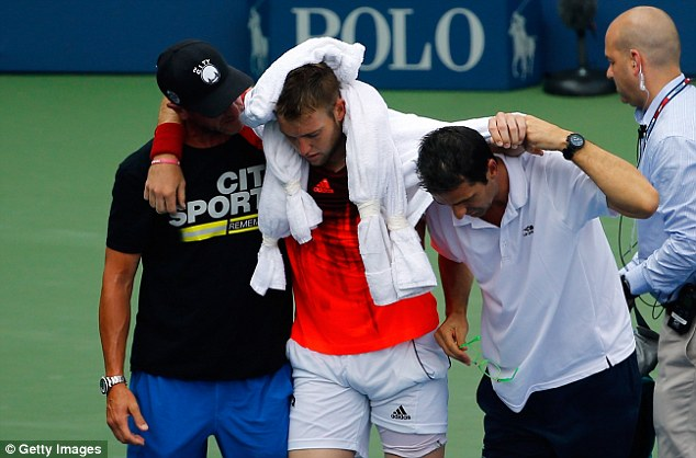 Sock is helped off the court by the trainer and is draped in ice towels