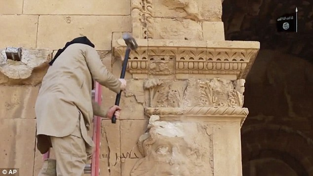 An ISIS militant hammers away at a face on a wall in Hatra, a large fortified city recognised as a UNESCO World Heritage site, 68 miles southwest of Mosul, Iraq in April