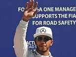 Mercedes Formula One driver Lewis Hamilton (C) of Britain celebrates after getting the pole position at the end of the qualifying session for the Italian F1 Grand Prix in Monza September 5, 2015. Ferrari Kimi Raikkonen (R) of Finland was second and Ferrari Sebastian Vettel (L) of Germany was third. REUTERS/Giampiero Sposito